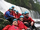 Corporate group infront of waterfall in brecon beacons on activity programme with Call of the Wild in wales